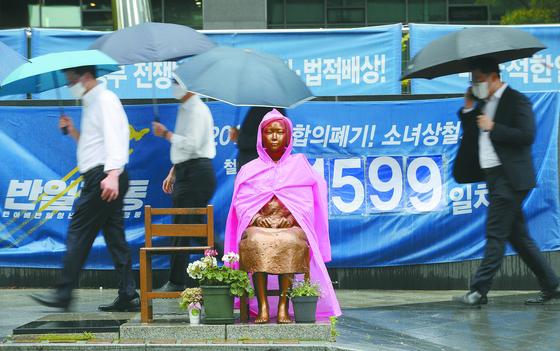 15일 오전 서울 종로구 수송동 옛 주한 일본대사관 앞에 있는 평화의 소녀상에 비옷이 입혀져 있다. [연합뉴스]