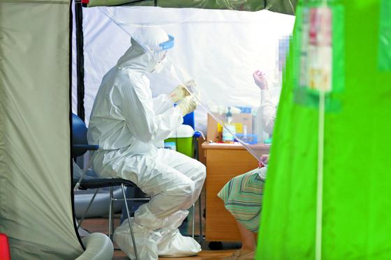 의대 정원 확대 정책을 놓고 의사단체와 병원 사이의 논쟁이 달아오르고 있다. 지난달 24일 광주 서구보건소 선별진료소에서 의료진이 코로나19 진단검사를 하고 있다. [연합뉴스]