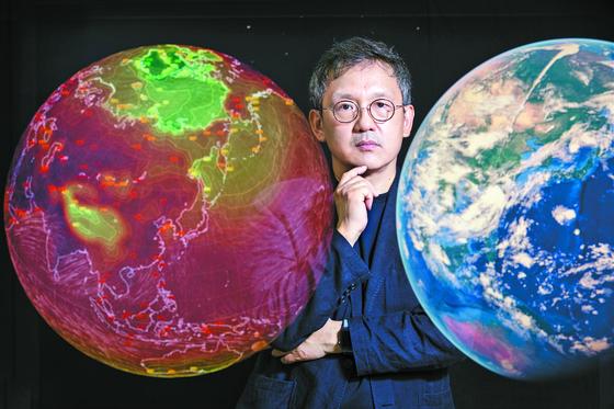 """조천호 교수가 푸른 지구와 뜨거워진 지구 사이에 섰다. 붉은색은 온실가스가 저감되지 않을 경우 2100년 지구의 평균기온을 나타낸 것이다. 색깔이 붉을수록 기온이 높다. 조 교수는 '온실가스를 줄이면 막을 수 있는 일""""이라고 말했다. 박종근 기자"""