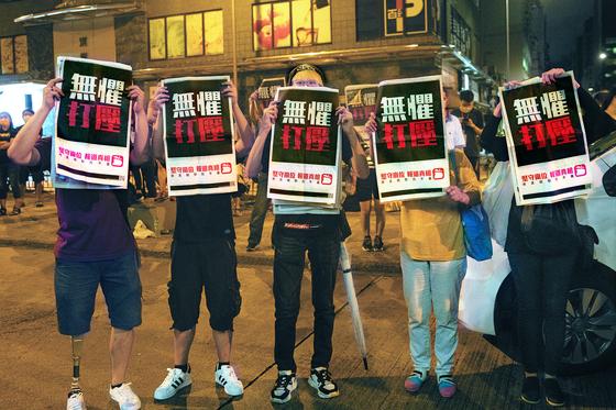 지난 11일 지미 라이 빈과일보 회장이 구금된 홍콩 몽콕경찰서 앞에서 지지자들이 신문을 들고 시위를 벌이고 있다. [EPA=연합뉴스]