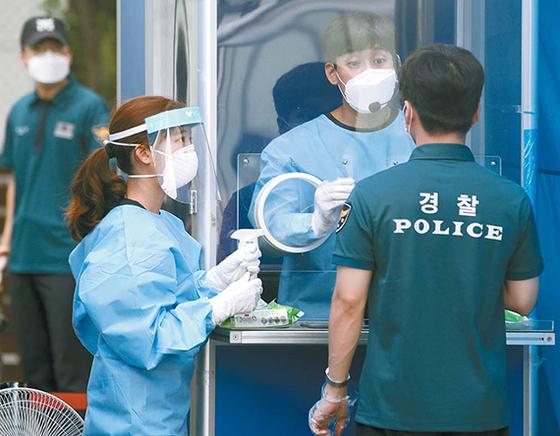서울 도심 광복절 집회에 투입된 경찰 관계자가 21일 서울 중구의 한 선별진료소에서 코로나19 검사를 받고 있다. [뉴시스]