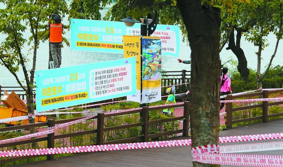 11일 오후 서울 송파구청 관계자들이 석촌호수 산책로에 시민들의 출입자제를 권고하는 현수막을 설치하고 있다. [뉴스1]
