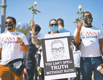 지난 23일 미국 워싱턴DC 대법원 앞에서 시민들이 흰 장미를 들고 루스 베이더 긴즈버그 연방대법관을 추모하고 있다. [AFP=연합뉴스]