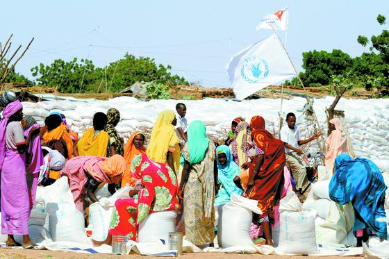 유엔 세계식량계획(WFP)이 올해 노벨 평화상 수상자로 선정됐다고 9일 노르웨이 노벨위원회가 발표했다. 사진은 2014년 아프리카 수단의 난민 여성들이 다르푸르 인근의 실향민을 위한 칼마 캠프에서 세계식량계획이 제공하는 구호 식량을 받는 모습. [AFP=연합뉴스]