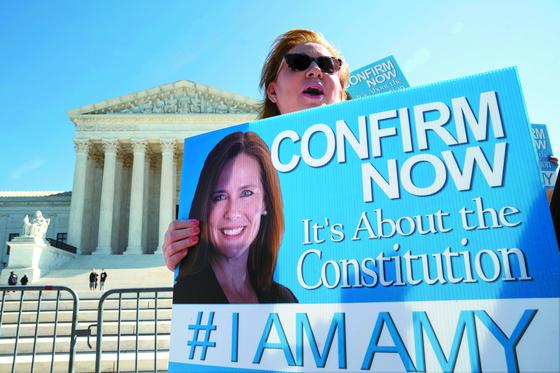 15일(현지시간) 미국 워싱턴DC 연방대법원 앞에서 한 시민이 에이미 코니 배럿 연방대법관 지명자의 상원 인준을 촉구하는 피켓을 들고 1인 시위를 벌이고 있다. [AFP=연합뉴스]