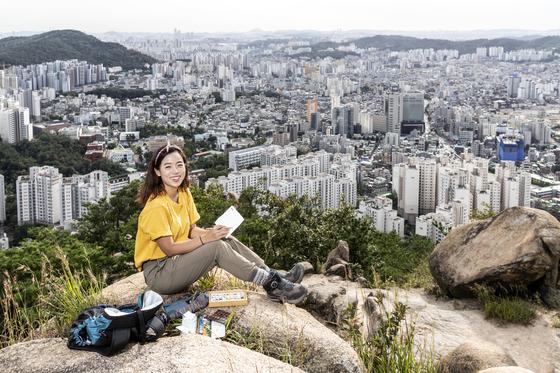 """'하이킹 아티스트' 김강은씨가 지난 9월 17일 북한산 족두리봉으로 이어지는 능선에서 그림을 그리고 있다. 깔개도 없이 앉은 그는 """"바위가 따뜻해서 좋다""""고 말했다. 김현동 기자"""