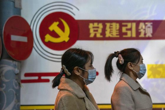 중국공산당 19기 5중전회가 폐막한 지난 29일 중국 베이징에서 마스크를 착용한 시민들이 공산당 로고와 '당 조직 강화를 통해 당이 사회발전을 이끈다(黨建引領)'는 내용의 슬로건이 적힌 간판 앞을 지나가고 있다. [AP=뉴시스]