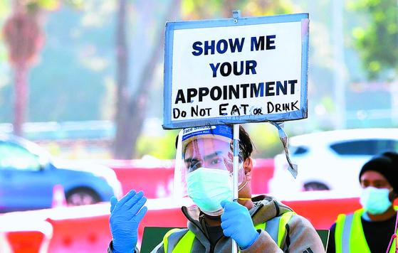 12일(현지시간) 미국 LA의 코로나 진단 검사장에서 한 자원봉사자가 '예약증을 보여달라'는 안내판을 들고 있다. [LA AFP=연합뉴스]