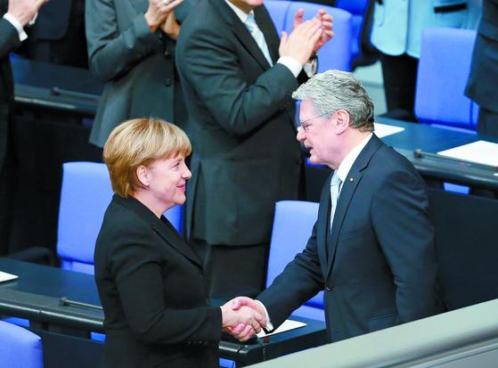동독 시절 목사였던 요아힘 가우크 전 독일 대통령(오른쪽)이 2012년 3월 23일 베를린 분데스탁(연방하원)에서 열린 대통령 취임식에서 앙겔라 메르켈 총리와 악수하고 있다. 메르켈 총리의 아버지도 동독 개신교 목사로 활동했다. [로이터=연합뉴스]