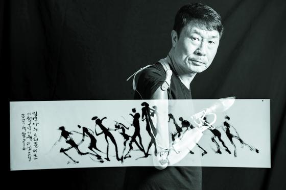 의수에 붓을 끼운 석창우 화백. 그림은 2009 세계피겨선수권 우승 당시 김연아의 트리플 러츠 점프를 표현한 것. 박종근 기자