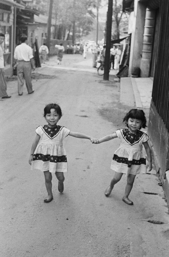 한영수 사진가의 작품. 똑같이 원피스를 맞춰입은 쌍둥이 자매의 세련된 패션이 눈에 띈다. 서울, 명동, 1960년. [사진 한영수 문화재단]