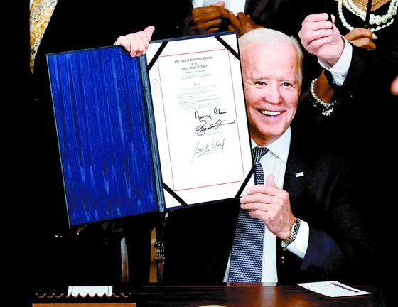조 바이든 미국 대통령이 17일 백악관에서 노예해방기념일인 6월 19일을 공휴일로 지정하는 법안에 서명한 뒤 활짝 웃고 있다. [로이터=연합뉴스]