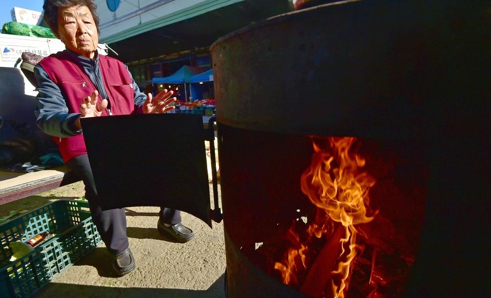 절기상 첫눈이 내린다는 소설(小雪)인 22일 인천시 남동구 농산물도매시장에서 한 상인이 불을 쬐고 있다. 기상청은 오늘 아침 최저기온이 영하권으로 떨어지며 강추위가 찾아올것으로 예보했다. 윤상순기자